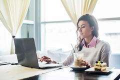 Woman working on laptop notebook computer at cafe, internet distance work, business lunch. Stock Photos
