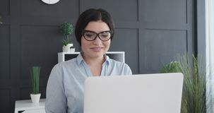 Woman working on laptop at office. Happy businesswoman working on laptop at office stock video footage