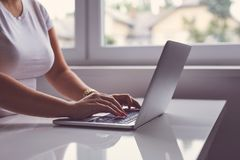 Woman working on a laptop in office. Toned stock photos