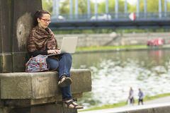Woman working on laptop outdoors in the sity. Freelance specialists. Royalty Free Stock Photos