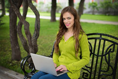Woman working on laptop in the park Stock Photography
