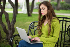 Woman working on laptop in the park Royalty Free Stock Images