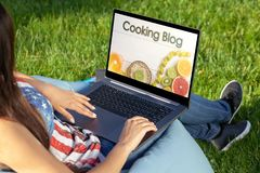 Woman working on laptop pc computer with with her culinary blog, sitting in park on green grass sunshine lawn outdoors. Close up hands on keyboard. Woman royalty free stock photos