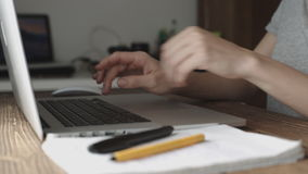 Woman working with laptop placed on wooden desk. Woman working with laptop on modern wooden desk, angled notebook on table in home interior, soft focus stock video footage