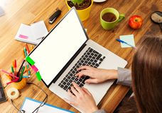 Woman working on laptop. Woman working with laptop placed on wooden desk. Shot from aerial view Stock Photos
