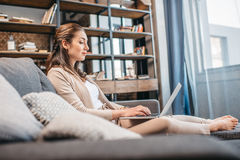 Woman working on laptop while relaxing on sofa at home Stock Photos