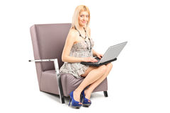 Woman working on a laptop seated in an armchair Royalty Free Stock Images