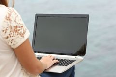 Woman working with a laptop and showing the display Stock Photography