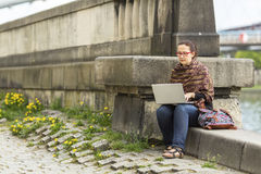 Woman working on laptop while sitting near the river promenade in the old town. Royalty Free Stock Image