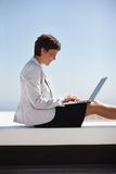 Woman working on a laptop while sitting outdoors Stock Photos