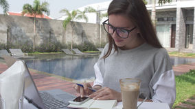 Woman working on laptop and smartphone near pool on tropical luxury villa . Female work on computer and mobile phone. Business online. Hot chocolate cacao on Royalty Free Stock Photos