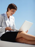 Woman working on a laptop smiling over the blue sky Stock Images