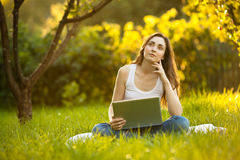 Woman working on laptop stiiting on the green grass Royalty Free Stock Image