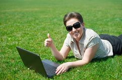 Woman working on laptop in summer outdoor, lie on your belly on green grass meadow, show best gesture, happy people, city park Stock Photography