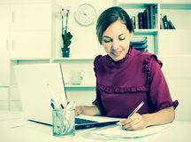 Woman working with laptop and taking notes. Beautiful business woman working at office with laptop and taking notes Stock Photos