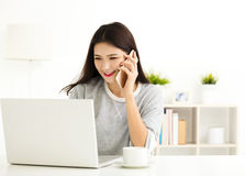 Woman working on laptop and talking on the phone Royalty Free Stock Photo