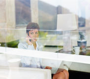 Woman working on a laptop through a window pane Royalty Free Stock Photos