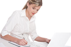 Woman working with laptop and writing notes Royalty Free Stock Photography