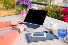 Woman working with tech gadgets outdoors. Woman working with macbook ipad and iphone in cafe outdoors Royalty Free Stock Images