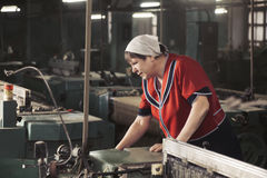 Woman working on the machine sideview Royalty Free Stock Image