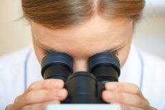 Woman working with a microscope. Royalty Free Stock Photo