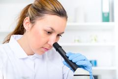 Woman working with a microscope in a lab Stock Image
