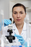 Woman working with a microscope in a lab.Toning image Stock Photo