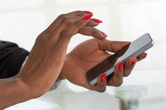 Woman working with a mobile phone above business documents Stock Photography