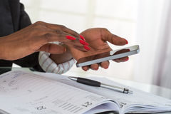 Woman working with a mobile phone above business documents Stock Photos
