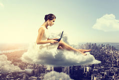 Woman working o a cloud. Above the city Royalty Free Stock Photos