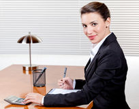 Woman Working in Office. An attractive young woman happily works at her desk in her office Royalty Free Stock Photos