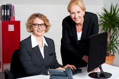 Woman working in office with colleague Royalty Free Stock Photo