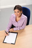 Woman working in office looks up while writing Stock Images