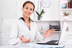 Woman working office. Portrait of glad young business woman working on computer at firm office Royalty Free Stock Photos