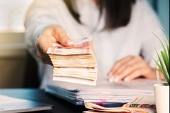 Woman working at office. Recount of bank note. Hand giving money close up stock images