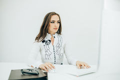 Woman working in office, sitting at desk, using computer Stock Image