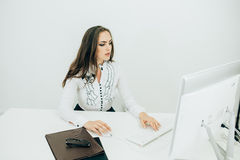 Woman working in office, sitting at desk, using computer Royalty Free Stock Images