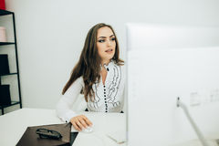 Woman working in office, sitting at desk, using computer Stock Photos