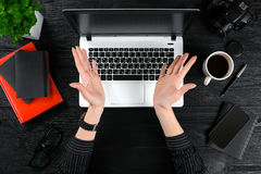 Woman working at the office table. Top view of human hands, laptop keyboard, a cup of coffee, smartphone, notebook and a Stock Images