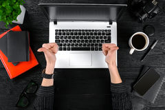 Woman working at the office table. Top view of human hands, laptop keyboard, a cup of coffee, smartphone, notebook and a Stock Photo