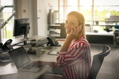 Woman working in office and talking on smart phone. Business woman working in office and talking on smart phone Stock Images