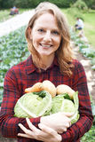 Woman Working On Organic Farm Holding Produce. Portrait Of Woman Working On Organic Farm Holding Produce Royalty Free Stock Photography