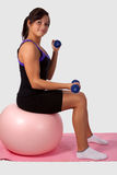 Woman working out. Attractive young brunette woman wearing workout attire sitting on a large pink exercise ball lifting weights over white Royalty Free Stock Photos