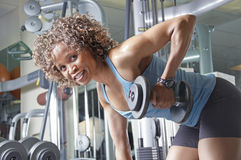 Woman working out. An African American woman working out in the gym with weights Stock Image