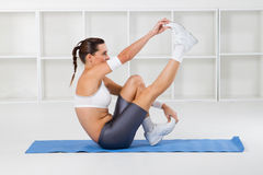 Woman working out. A pretty young fitness woman working out and stretching on gym mat Royalty Free Stock Images