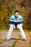 Woman Working Out. Young woman exercises out side in a park stock image