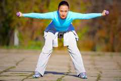 Woman Working Out. Young woman exercises out side in a park royalty free stock photo