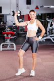 Woman working out. Fitness woman working out with dumbbell in gym Royalty Free Stock Photo