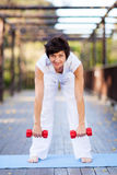 Woman working out. Happy middle aged woman working out with dumbbells Royalty Free Stock Images