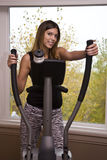 Woman working out. Young woman working out on an eliptical machine Stock Images
